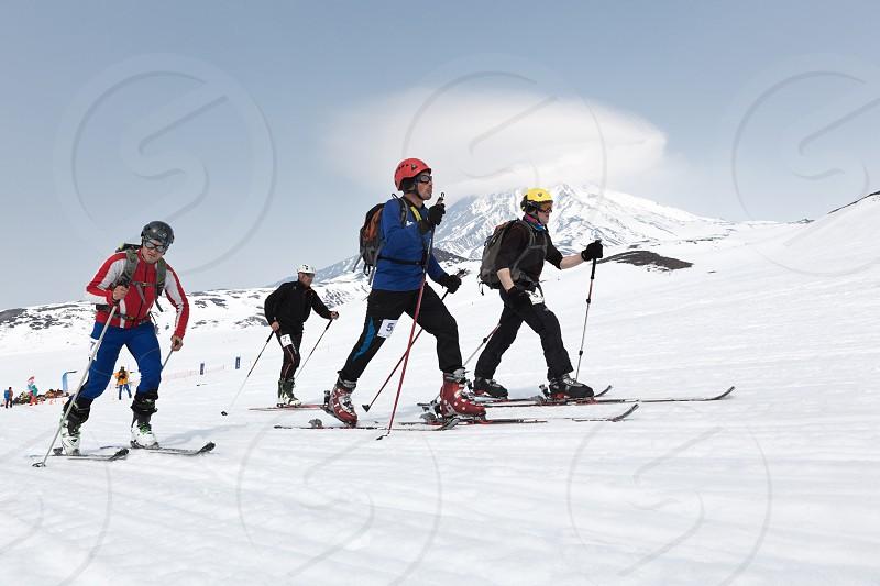 AVACHA KORYAK VOLCANOES KAMCHATKA RUSSIA - APRIL 27 2014: Ski mountaineers climb on skis on mountain. Team Race ski mountaineering Asian ISMF Russian Kamchatka Championship. photo