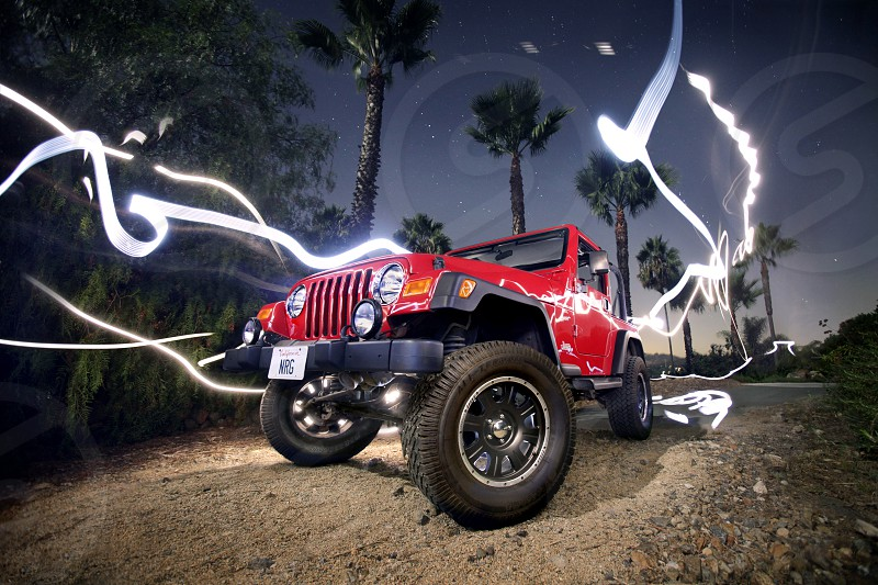 Ribbons of light energy dances around a red off-road lifted jeep at night evening twilight on a dirt road under a line of palm trees and shrubs. Purple sky black rims.  photo