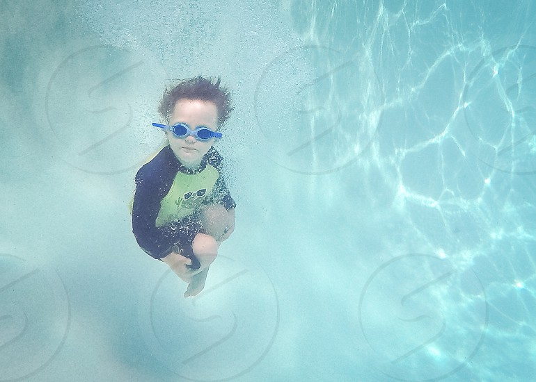 Boy doing cannonball underwater swimming in pool photo
