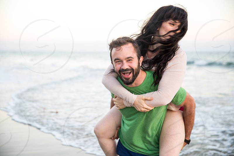 smiling man in green crew neck shirt carrying woman in white long sleeve shirt from behind near ocean water under sunny sky photo