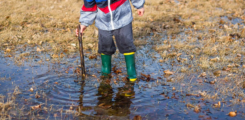 Child playing with a stick in puddles wearing rainboots photo