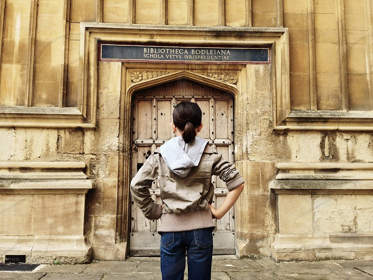 woman in brown and grey hoodie standing in front of bibliotheca bodleina photo