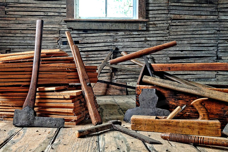 Wood cutting and woodworking tools piled in a room of an old house photo