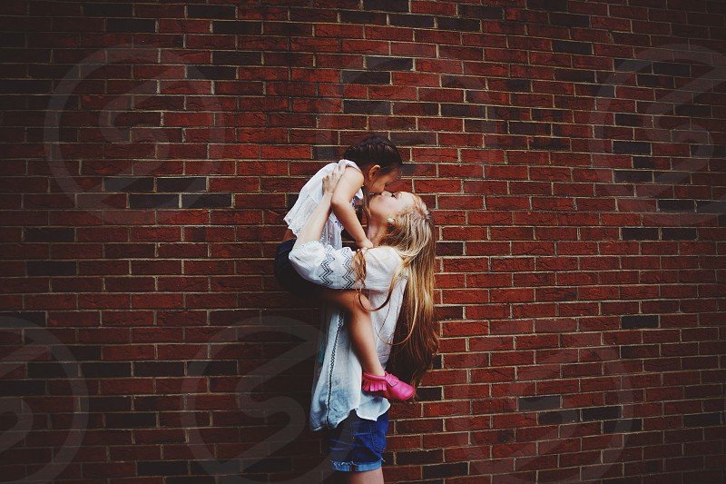 blonde woman in white holding a little girl in the air giving her a kiss by a red brick wall photo