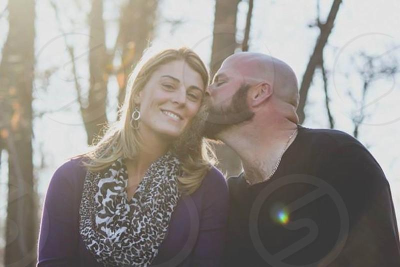 man with beard kissing woman in cheetah scarf on cheek outside photo