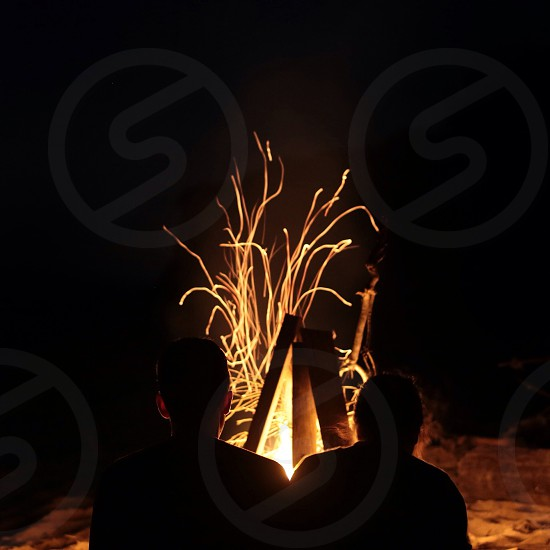 people sitting in front of campfire photo