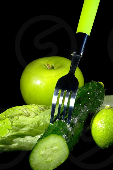 group of green vegetables and fruits with fork over black background photo