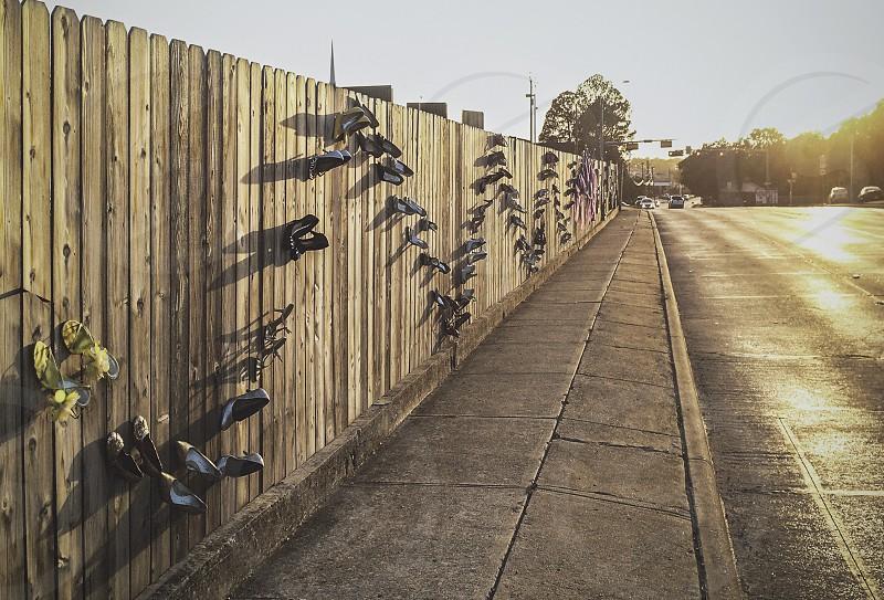 Weird fence along a street at golden hour.  photo