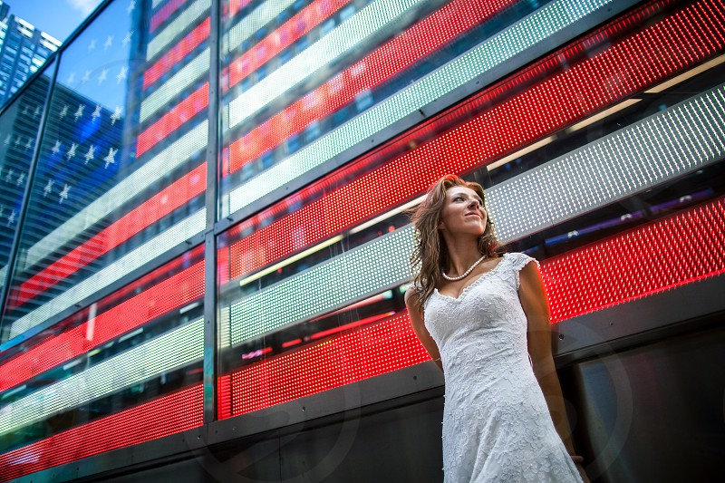 Young woman dressed in bridal (type) gown standing in front of the American Flag in Times Square in New York City NY. photo