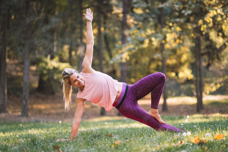 Young woman doing yoga in the park in autumn photo