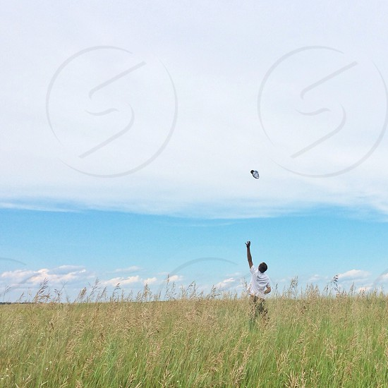 man wearing a white shirt throwing something in the air photo