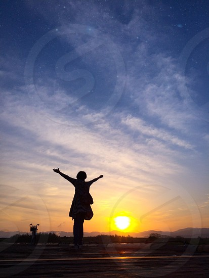 person standing in sunset photo