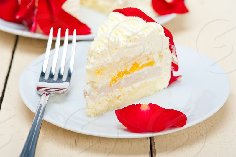 whipped cream mango cake with red rose petals photo