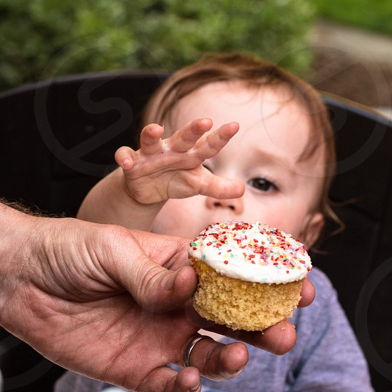 Close-up of man's hand holding a cupcake with baby reaching for it. photo