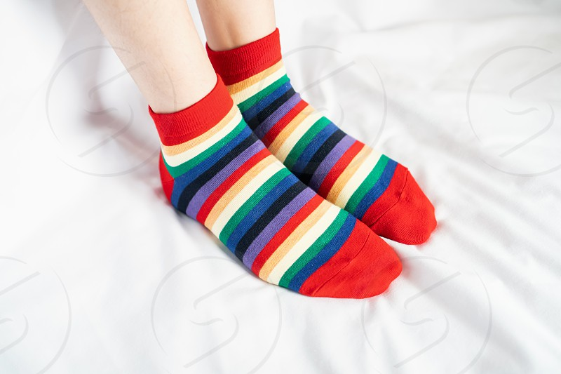 Women's legs in socks colors alternating side stand on white fabric floor. photo