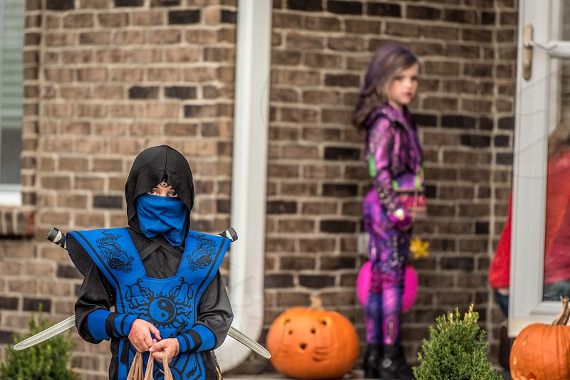 Boy in a ninja costume walking away from a house after getting candy during Trick or Treat on Halloween. photo
