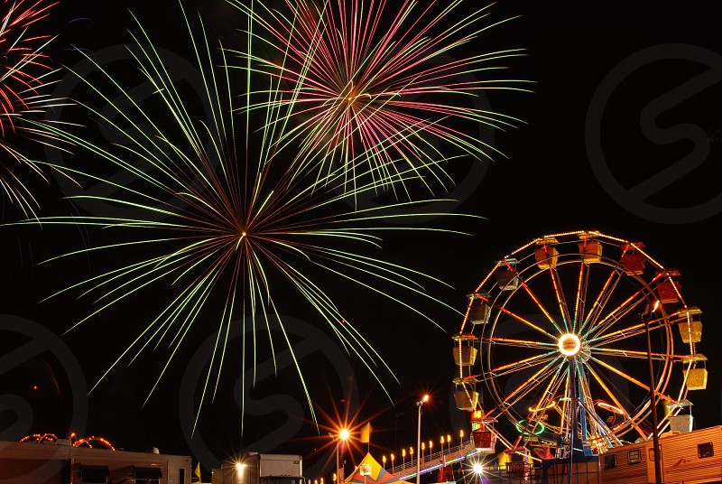 fireworks exploding behind a carnival ferris wheel photo
