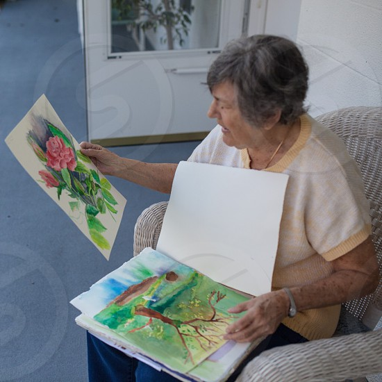 Elderly woman showing her personal paintings.  photo
