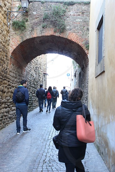 focus photo of people walking between brown bricked wall building during daytime photo