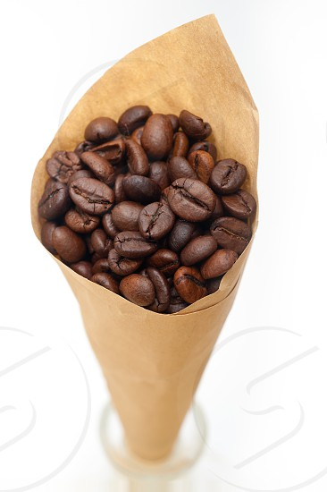espresso coffee beans on a paper cone cornucopia over white background photo