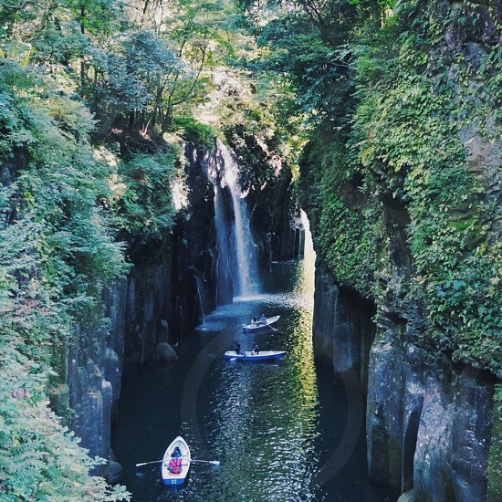 people riding blue and white kayaks near waterfalls and beside green trees photo