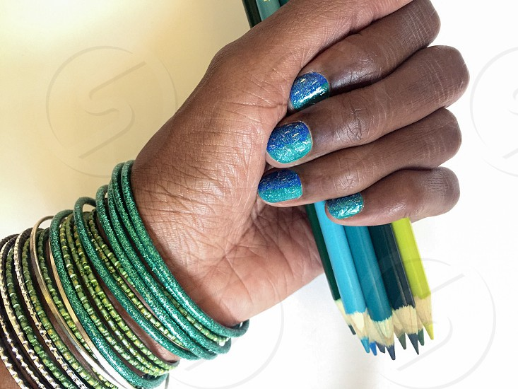 A hand with pretty painted blue glittery nails and blue green bangles round the wrist clutches a bunch of various blue pencils photo