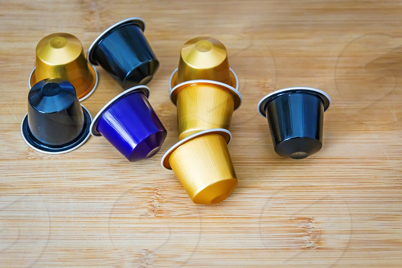 group of espresso coffee capsules with a wooden background photo