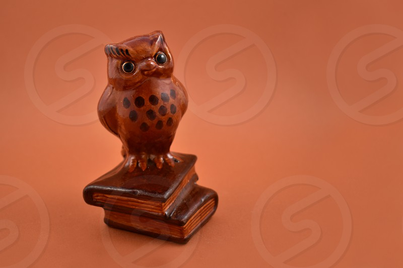Wise owl figurine. Owl figurine on a brown background. Brown owl on a pile of books photo