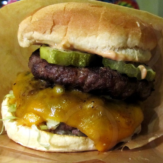 Cheeseburger with thick pickles on seedless bun photo