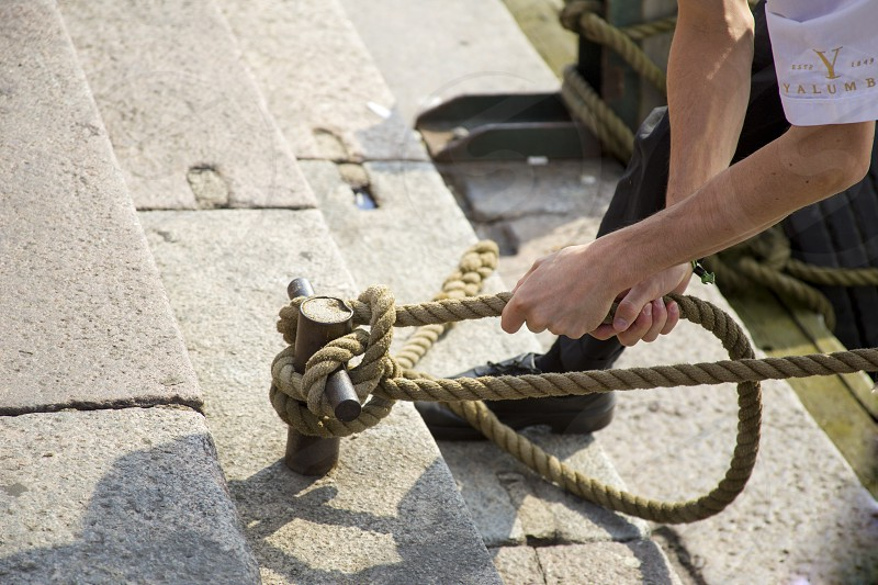 The sailor ties the rope to the post on the dock. photo