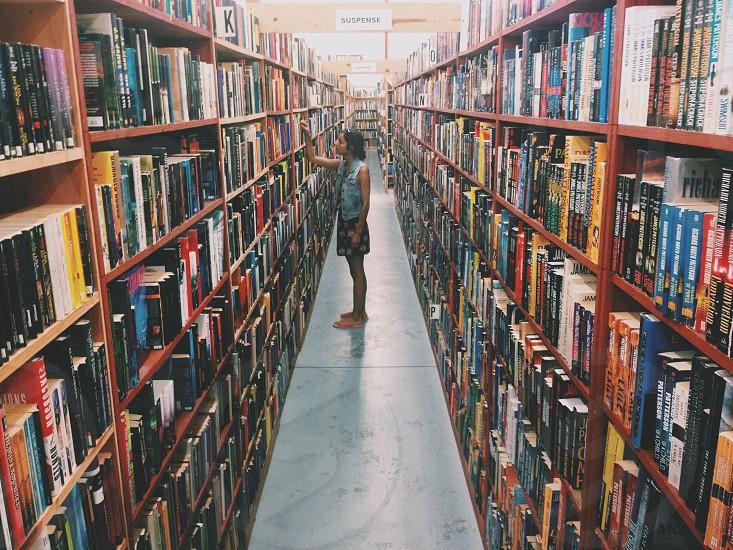 woman standing between bookshelves photo