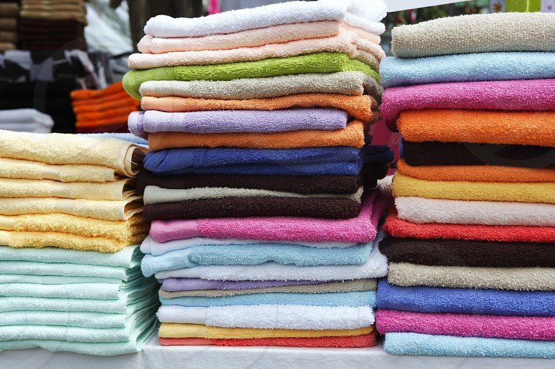 colorful bathroom towels stacked on rows in market photo