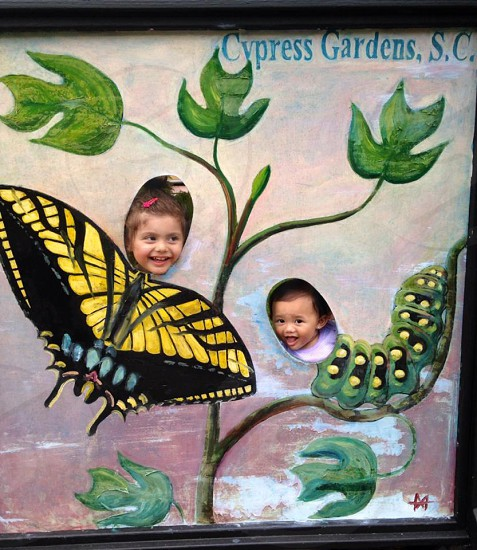 two children peeking on caterpillar and butterfly board with holes photo