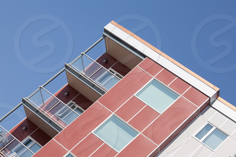 Upper corner of modern apartment condominium high rising building stretching angled into blue sky photo