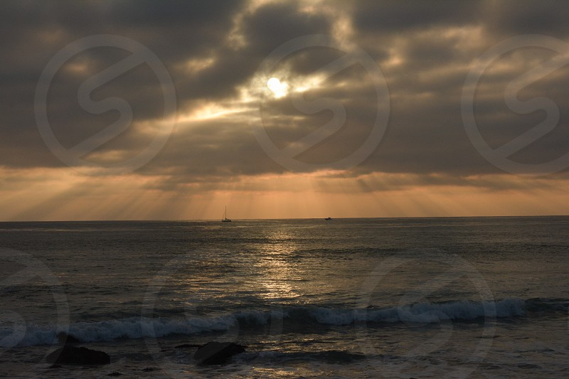 sun covered by gray clouds above ocean waves photo