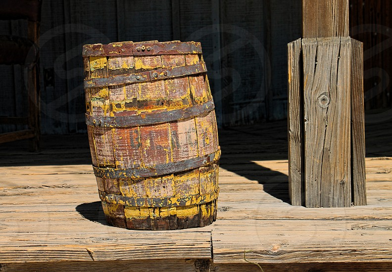 Old weathered wooden barrel leans to the side on a wooden porch photo
