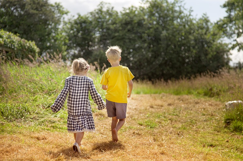 girl and boy walking on green and brown field photo
