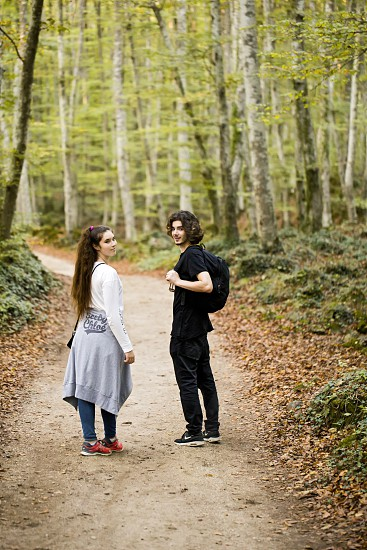 A young man and girl walking in a beech forest. photo