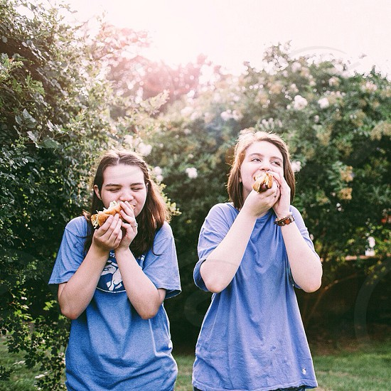 two woman in blue t shirt standing and eating photo