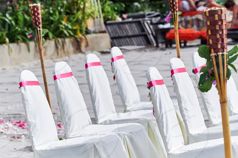 Wedding chairs Spandex white cover decorating with red pink organza sash line up for beach wedding venue settings photo