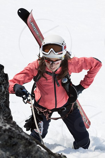 AVACHA VOLCANO KAMCHATKA PENINSULA RUSSIA - APR 21 2012: Open Cup of Russia on Ski Mountaineering on Kamchatka - young woman ski mountaineer climbing on rope on rock with skis strapped to backpack photo