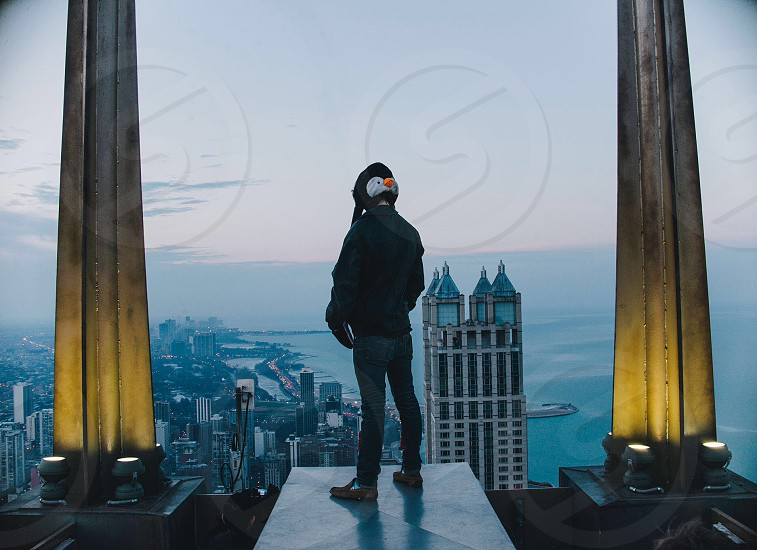 man standing at top of building photography  photo