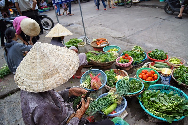 person holding vegetable near vegetable display photo
