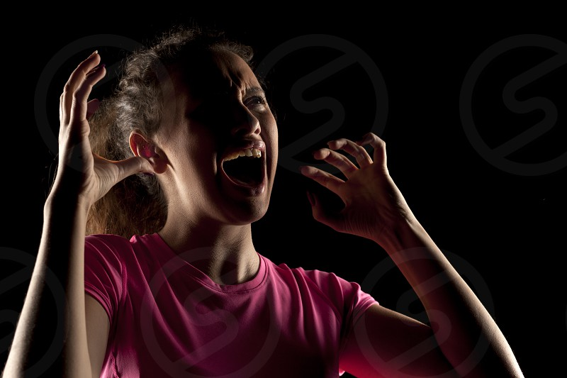 screaming unknown woman with the face in the shadow photo