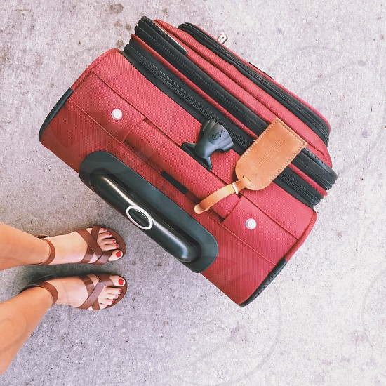 woman wearing brown sandals standing near red and black luggage photo