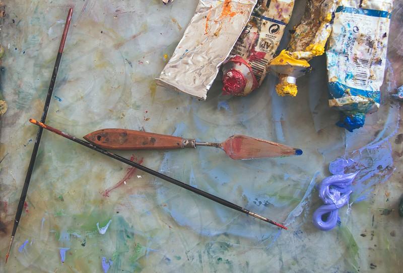 black paint brush beside red dye photo