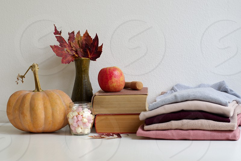 Pumpkin on a table - pile of clothes and books next to it photo