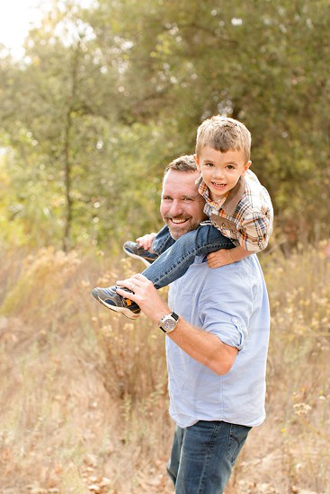 man carrying a boy on his shoulders with wheat grass and trees on the background during daytime photo