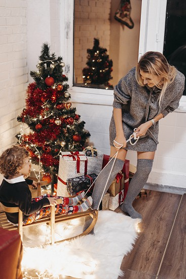 Mother and sun sitting on a floor and firing sparklers in Christmas decorated studio photo
