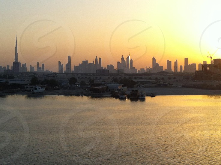 silhouette of high-rise buildings near body of water photo